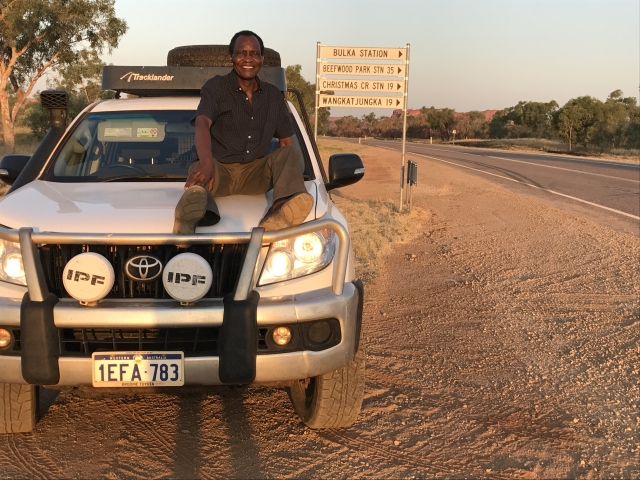 man-sitting on-bonnet-of-his-car