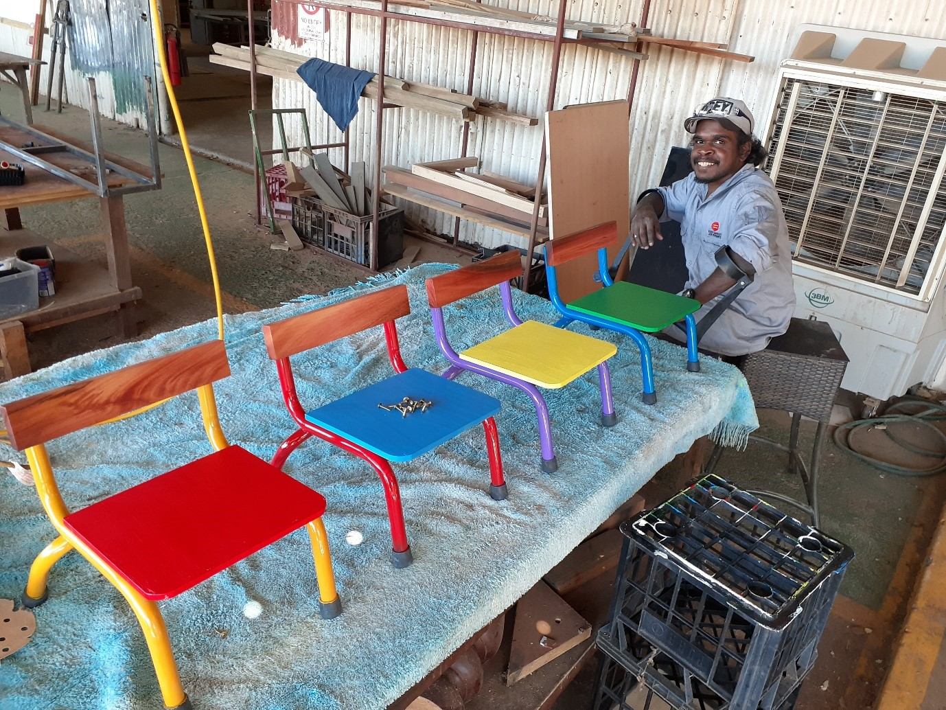 man-standing-in-workshed-showing-off-chairs