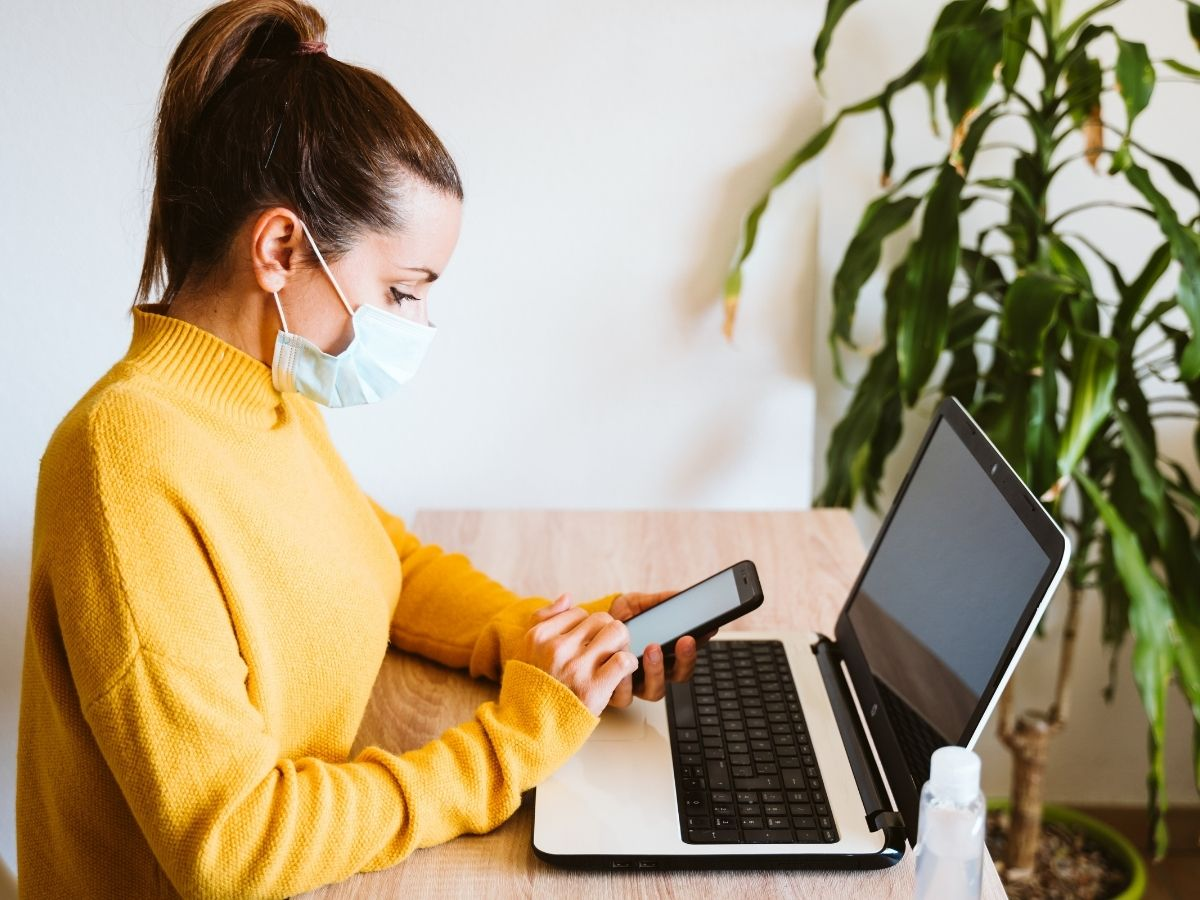 woman-wearing-mask-and-looking-at-phone-and-computer-to-stay-updated-covid-19